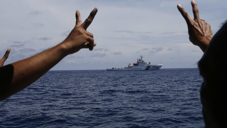 Philippine crewmen gesture towards a Chinese ship in the contested area of the South China Sea.