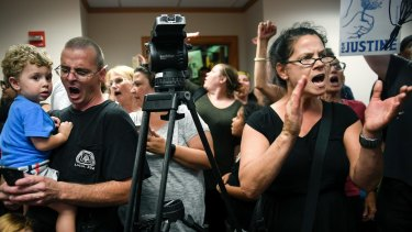 Protesters chant slogans against Minneapolis mayor Betsy Hodges during her press conference.