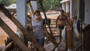 People stand in their damaged home in Barra Longa after a dam burst in Minas Gerais state, Brazil.