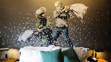Banksy's wall painting showing an Israeli border policeman and a Palestinian in a pillow fight in one of the suites of the Walled Off Hotel.
