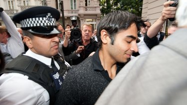 Caught: Pakistani cricketer Salman Butt is escorted by police through a media scrum in London in 2010.