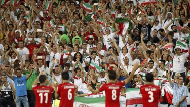 Fan club: Iran players celebrate victory over Qatar with their supporters