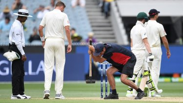 A groundsman takes a sledgehammer to the MCG pitch today.