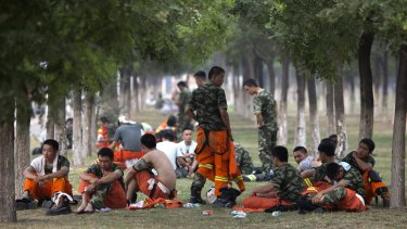 Chinese firefighters rest as they wait to be deployed near the site of the blasts.