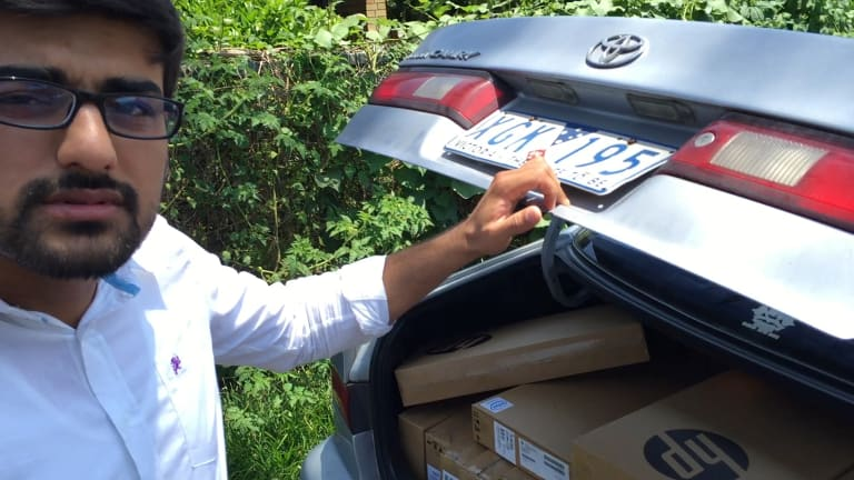 """Vocational education salesman """"Hamza"""" and his car full of laptops."""