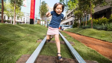 At the Future Street Project at Circular Quay, four-year-old Madeleine Boxsell jumps light rail tracks surrounded by grass.