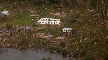 Debris is scattered around damaged buildings at Muamua on Vanua Blava Island in Fiji, after Cyclone Winston tore through the island nation. .