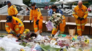 Volunteers from the Rural Fire Service removed flowers from the Martin Place memorial on December 23. The flowers will form part of a permament memorial.