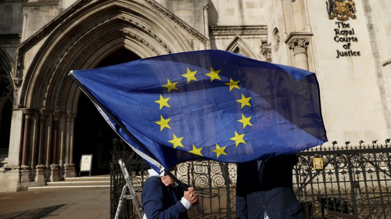 A pro-EU membership supporter holds an EU flag outside the High Court.