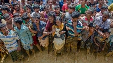 Rohingya Muslims, who crossed over from Myanmar into Bangladesh, wait to receive handouts near Balukhali refugee camp, Bangladesh.