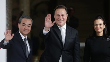 Chinese Foreign Minister Wang Yi, left, waves with Panamanian President Juan Carlos Varela and Foreign Minister Isabel de Saint Malo, in Panama City, on Saturday,
