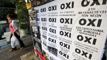 """A woman walks past referendum campaign posters reading """"No"""" in Greek in Athens."""