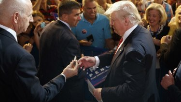 Republican presidential candidate Donald Trump is handed a pen as he signs autographs at a campaign rally in Fayetteville, North Carolina.