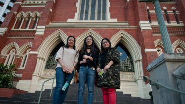 Chinese tourists Xinjie Lu, Ke Wany and Shunran Li are among the thousands of international tourists stopping now visiting the Albert Street Uniting Church.