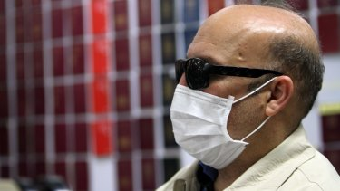 """After questioning, the passport """"doctor"""" admitted his own  passport was fake and his real name was Hamid Reza Jafary, of Iran. Here he is presented at a press conference in Bangkok on Wednesday, fake passports displayed int he background."""