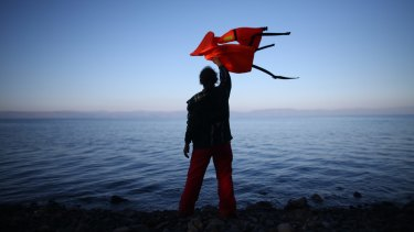 A woman waves a life jacket to direct a migrant boat ashore as it makes the crossing from Turkey to the Greek island of Lesbos.