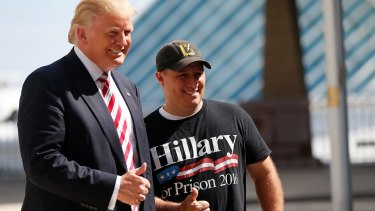 Mike Schuetz, a US Marine veteran and owner of Hawkins Guns, in Hawkins, Wisconsin, poses for photos with Republican Presidential candidate Donald Trump, left, at the Milwaukee County War Memorial Centre in Milwaukee, Wisconsin.