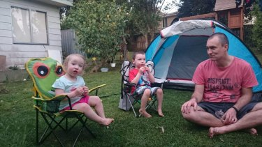 Eliza, 2, Lincoln, 4 and dad Martin Swinburn in the backyard of their Asquith home, which will likely be demolished and rebuilt, due to loose-fill asbestos found in the roof of the home.