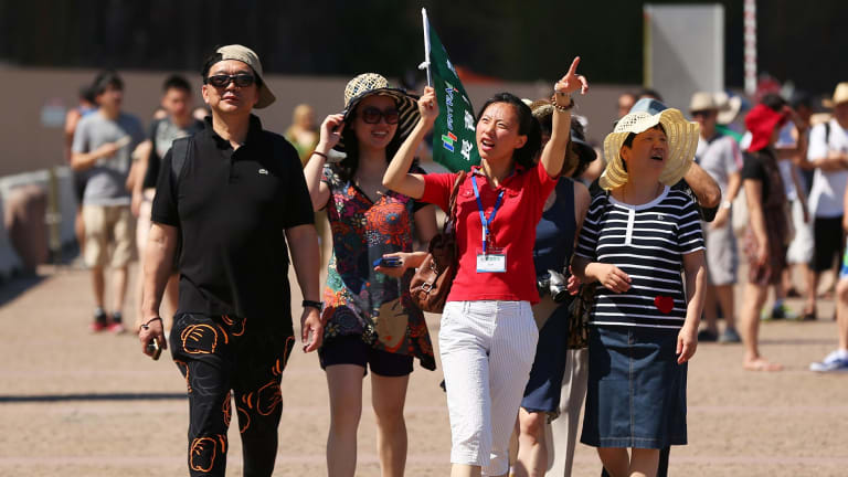 A tour guide leads a group of tourists towards the Sydney Opera House in Sydney: Australia needs to lift its game if it wants to attract more visitors.