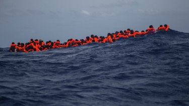 Sub-saharan migrants wait to be rescued in the Mediterranean Sea.