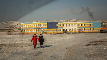 Coal smoke rises from a school's boiler as two girls walk home after class on the outskirts of Ulaanbaatar.