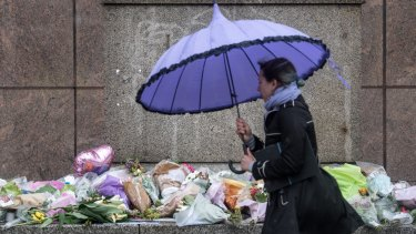 A woman walks past flowers and tributes left near the scene of Saturday's terrorist attack.