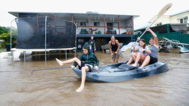 Kids paddle in a kayak as floodwaters inundate their yard in Murwillumbah.