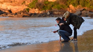 Heartbroken: Justine Damond's brother, Jason Ruszczyk with his wife, Katarina Ruszczyk, at the water's edge at Freshwater Beach during a vigil on Wednesday.