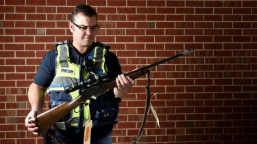 Leading Senior Constable David Jenkin - seen here with a gun seized from illegal deer hunters - is a serving officer in rural Victoria.