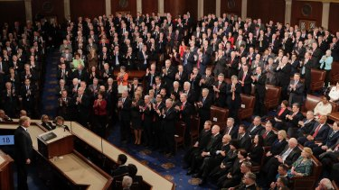 Republicans Congressional members stand and applaud as Democratic members sit as US President Donald Trump pauses during his address.