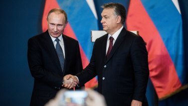 Vladimir Putin and Viktor Orban shake hands in Budapest.