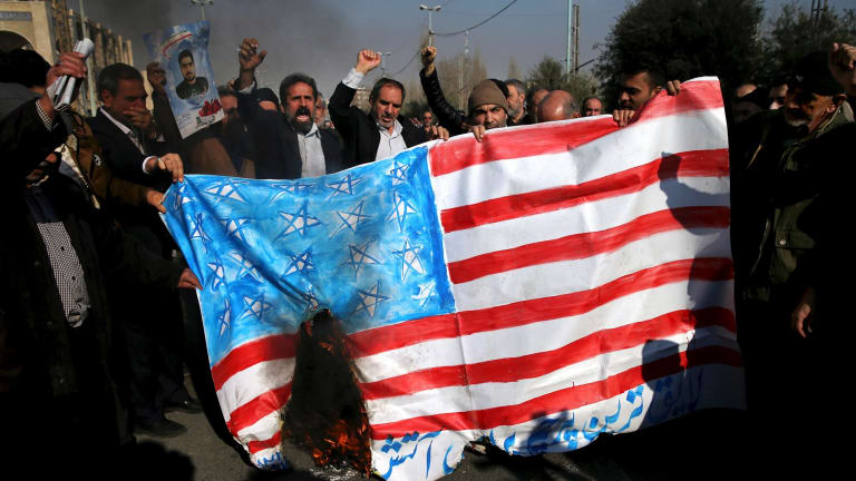 Iranian protesters chant slogans while they burn a representation of US flag on Friday.