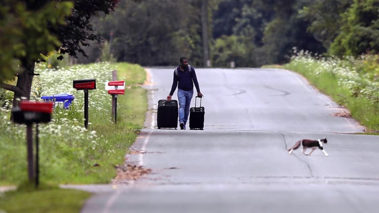 Dulne Brutus, of Haiti, tows his luggage down Roxham Road in Champlain, New York, while heading to an unofficial border station across from Saint-Bernard-de-Lacolle, Quebec.