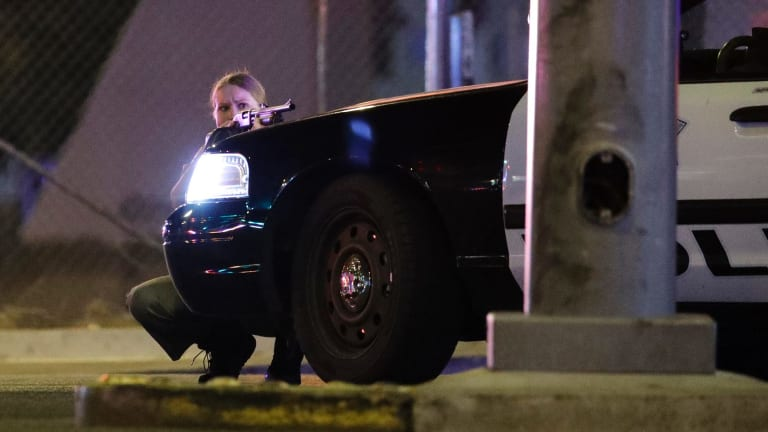 A police officer takes cover behind a police vehicle during a shooting near the Mandalay Bay resort and casino on the Las Vegas Strip.