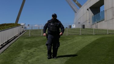 A security guard patrols the lawns at Parliament House.