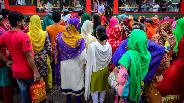 Garment workers cross a street on their way to work in Dhaka, Bangladesh.