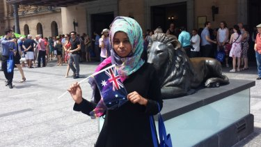 Fatuma Ali Hussein waves an Australian flag after the citizenship ceremony at City Hall.