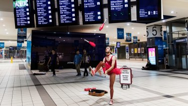 Sam Floyd aka 'Legs And His Magnificent Mind Bending Appendages' performs for early morning travellers at Flinders Street Station.