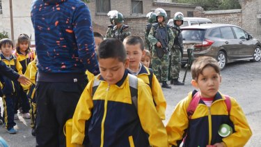 Children leave school under armed guard in Urumqi, Xinjiang, China.