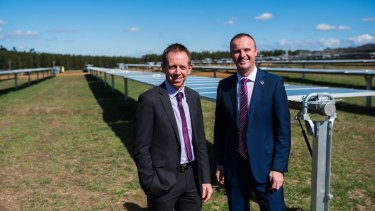 Ministers Shane Rattenbury and Andrew Barr at the Mugga lane solar farm in October 2016: Renewables scheme to cost each household about $144 a year in 2020, then fall away till Canberrans are making money on the deal.