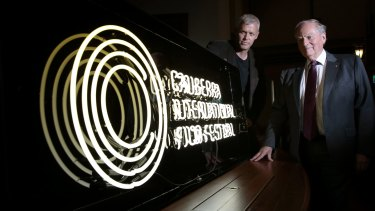 Canberra International Film Festival boardmember Cris Kennedy and general manager Andrew Pike with the neon sign made to promote the festival at the National Film and Sound Archive.