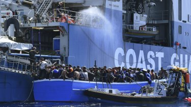 Some of the 441 refugees attempting to cross from Libya to Europe on a wooden boat are rescued by the Swedish Coast Guard off Libya.