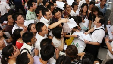 Jobseekers pass their resumes to representatives from Foxconn Technology Group at a job fair in Zhengzhou, Henan province.