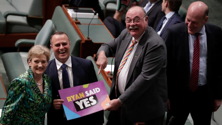 """Liberal MPs Jane Prentice, Tim Wilson and Warren Entsch hold up a sign saying """"Ryan said yes""""."""