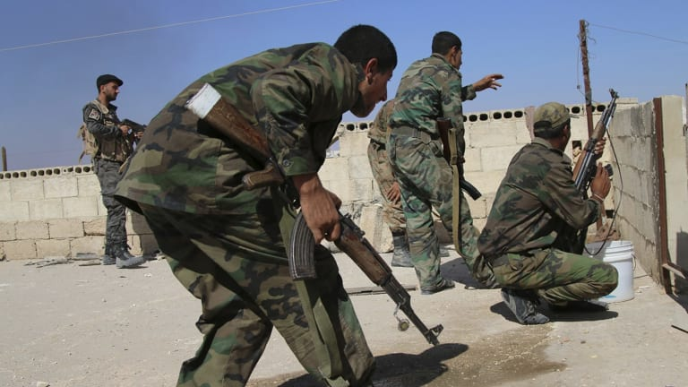 Syrian soldiers repel an attack in Achan, Hama province, Syria, on Sunday.