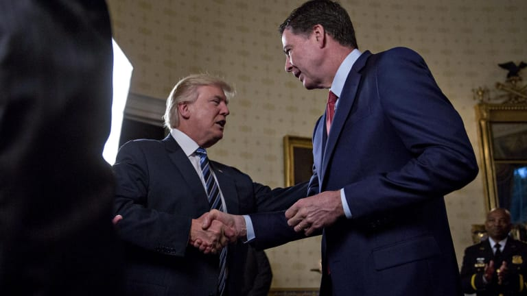 President Donald Trump greets James Comey during a reception at the White House on January 22.