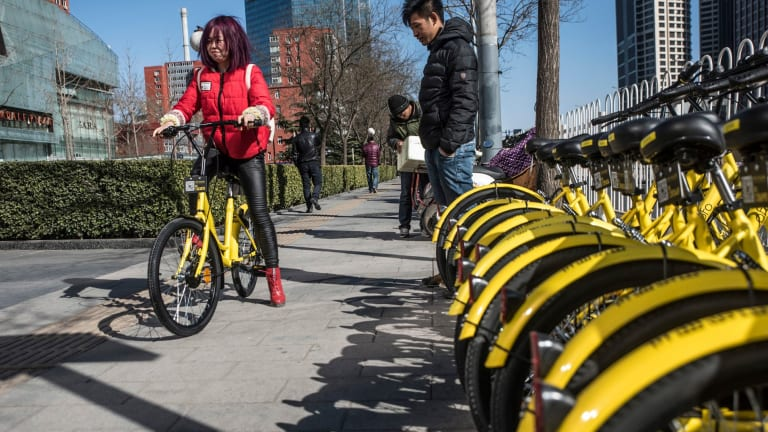 Picking up an Ofo bike. Commuters can pick up the bikes, ride them, then drop them off anywhere they like.