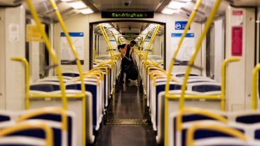 A cleaner clears the mess on a train bound for the city from Sandringham.
