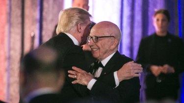 Billionaire bromance: President Trump and Rupert Murdoch embrace at a dinner honouring war veterans in May.
