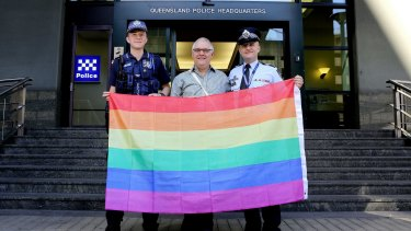 Transgender police officer Constable Mairead Devlin with Brisbane LGBTIQ Action Group convener Phil Brown and QPS LBGTIQ Support Network convener Sergeant Mick Gardiner stand proud with the rainbow flag outside the Brisbane police headquarters on Roma Street.